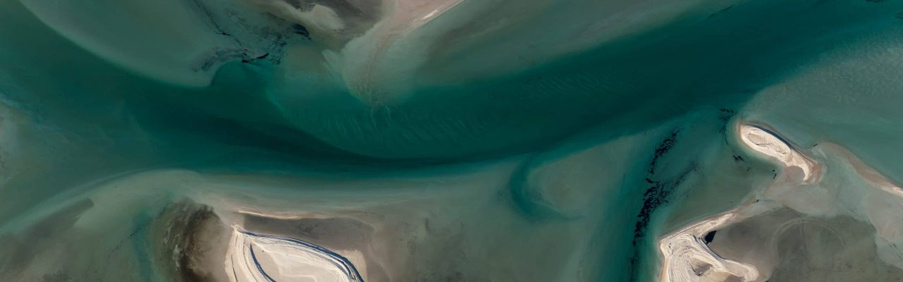 Aerial view of Multi Colored Tidal Water Channels Transforming the White Sand Banks on a Sunny Day at Shark Bay Western Australia